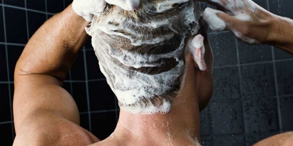A man washing his hair with shampoo