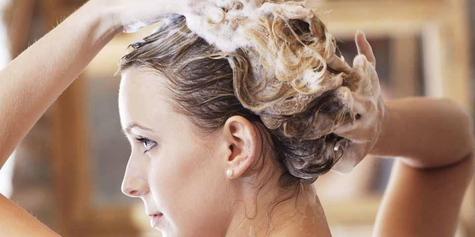 Woman who is applying shampoo on her hair