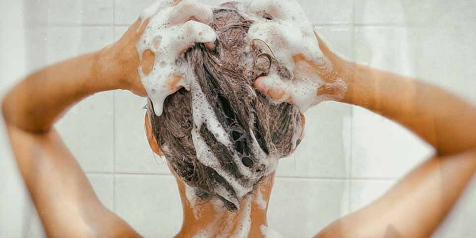 Woman who is massaging her scalp with an anti-dandruff shampoo
